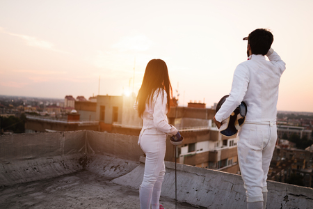 Two fencing athletes people practicing outdoor on rooftop