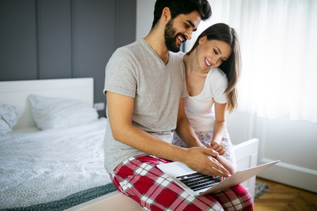 Young couple relaxing on bed with laptop. Love, technology, happiness, people and fun concept. Stock Photo