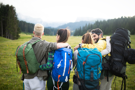 Four happy friends are looking on mountains and having fun together Reklamní fotografie - 124798387