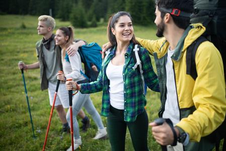 Avontuur, reizen, toerisme, wandeling en mensen concept - groep lachende vrienden met rugzakken en kaart buitenshuis