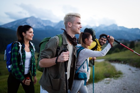 Four happy friends are looking on mountains and having fun together Reklamní fotografie - 124798402