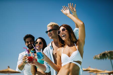 Gruppe von Freunden, die Spaß beim Sommerfest haben und Cocktails trinken Standard-Bild