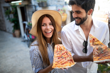 Couple eating pizza while traveling on vacation Stock Photo