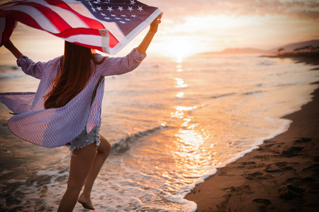 Happy woman running on beach while celebrateing independence day and enjoying freedom in USA 스톡 콘텐츠