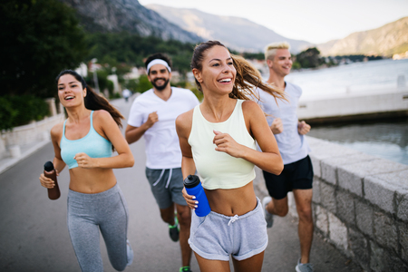 Outdoor portrait of group of friends running and jogging in nature