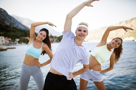 Group of happy friends or sportsmen exercising and stretching outdoor
