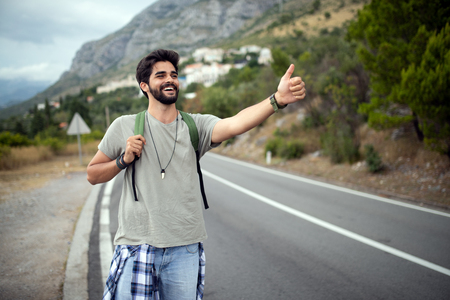 Hitchhiking young traveller man try to catch car on a forest road Stockfoto