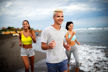 Group of young friends running and exercising on the beach Stock Photo