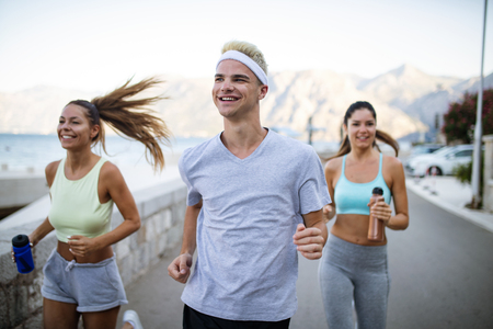 Group of young people friends running outdoors at seaside