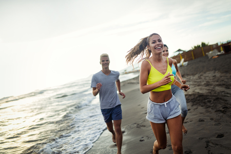 Group of sport people jogging on the beach