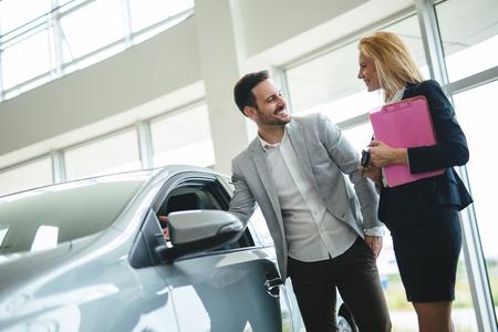 Portret szczęśliwego klienta kupującego nowy samochód