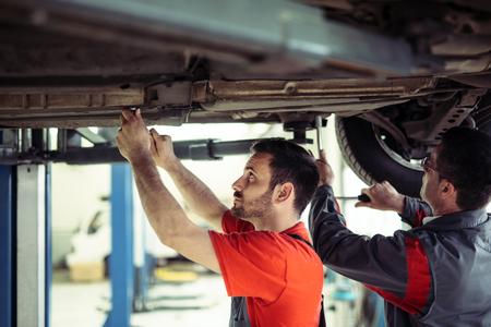 Auto mechanic working in garage. Repair service. Banco de Imagens - 124816818