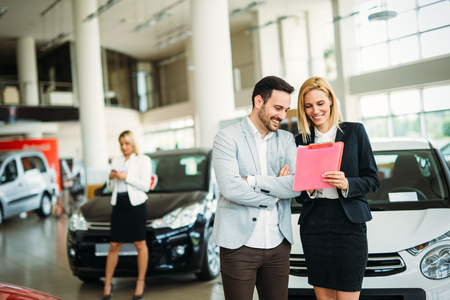 Group of happy car sales consultants working inside vehicle showroom