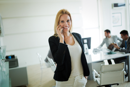 Portrait of businesswoman making call while business people working at background Banco de Imagens