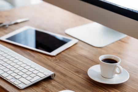 Escritorio de oficina con computadora, tableta y taza de café Foto de archivo