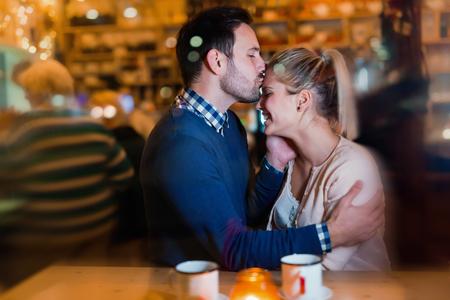 Gelukkig stel zoenen aan de bar en hebben een date