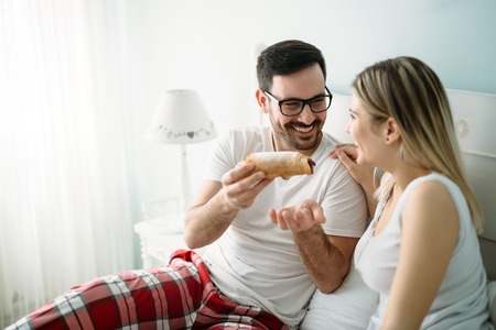 Young attractive couple having breakfast in bed Stock Photo
