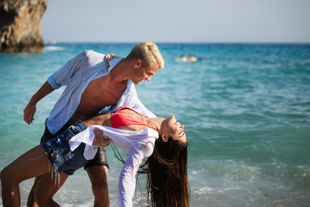 Happy young couple having fun and love at beach on sunny day Stock Photo