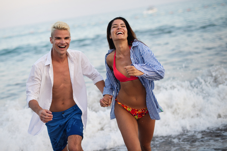Happy young couple having fun and love on the beach