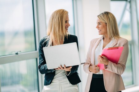Business women look and smile conversation with digital tablet in office