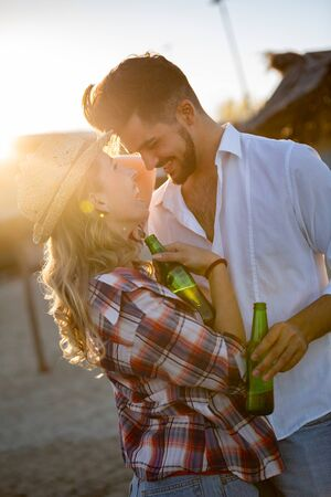 Happy young couple drinking beer and having fun at the beach Banco de Imagens - 124704569