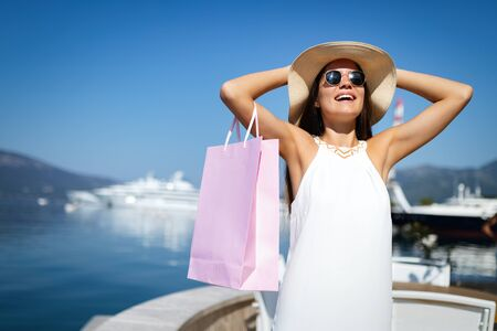 Shopping and tourism concept. Happy young woman with shopping bags