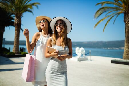 Shopping women happy holding shopping bags walking having fun laughing in street