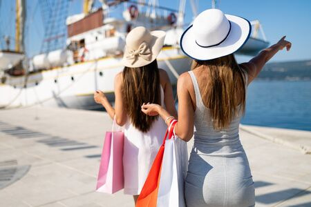 Shopping and tourism, vacation, happy, friends, people concept. Beautiful women with shopping bags Stock Photo