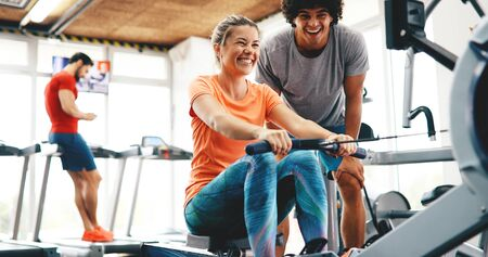 Personal trainer helping pretty woman reach goals