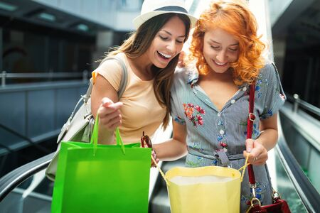 Happy women friends smiling and having fun while shopping together