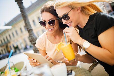 Schöne Mädchen, die Spaß haben, zusammen in einem Café im Freien zu lächeln