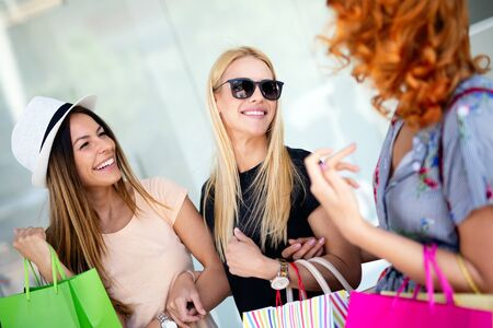 Young happy attractive girls with shopping bags in the city. Stock Photo
