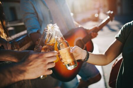 Group of friends having fun and playing guitar at summer Stock Photo