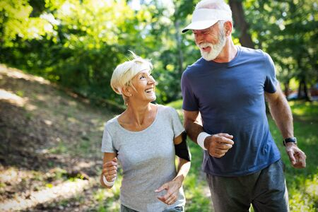 Mature couple jogging and running outdoors in nature Stock Photo
