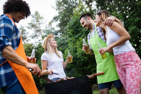 Group of happy friends eating and drinking beers at barbecue dinner