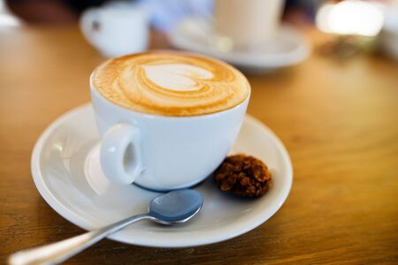 Cup with hot tasty coffee on wooden table in cafe, close up view Stock Photo