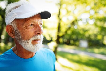 Portrait of athletic mature man after run. Handsome senior man resting after jog at the park Stock Photo - 124702831