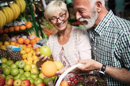 Portret van mooi bejaard echtpaar op de markt die voedsel koopt Stockfoto
