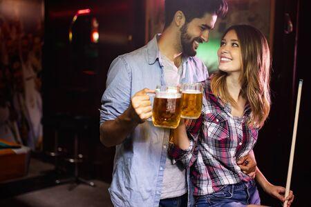 Pareja bebiendo cerveza y jugando al billar en fecha Foto de archivo