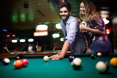 Couple dating, flirting and playing billiard in a pub Imagens