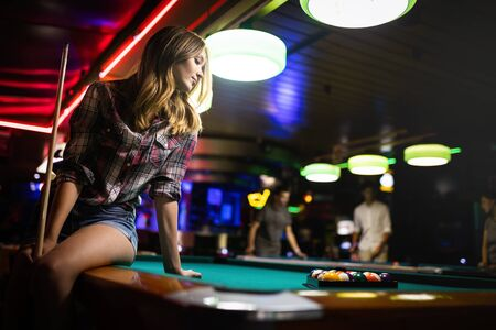 Young smiling girl playing billiard in club Imagens