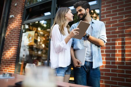 Travel, vacation, technology and friendship concept. Smiling couple with tablet in city