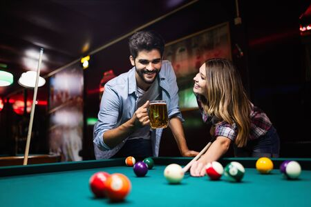 Young couple playing snooker together in bar Imagens