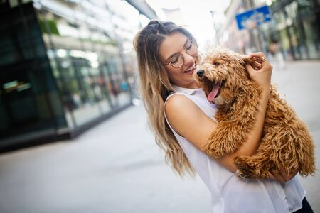 Happy woman with her dog smiling and palying outdoor Banco de Imagens - 124972058