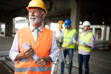 Confident construction engineer, architect, businessman in hardhat on building site
