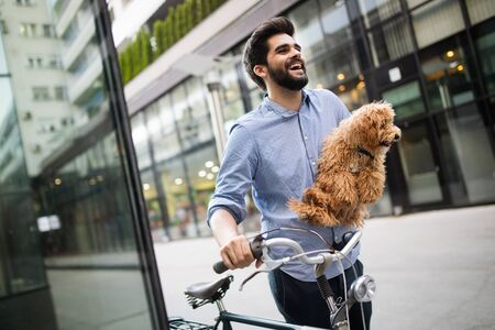 Happy young man holding dog in hands outdoors in city Banco de Imagens