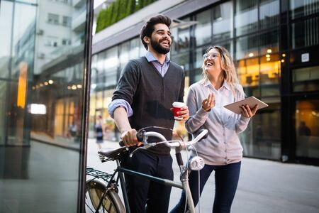 Young couple smiling and using technology in city