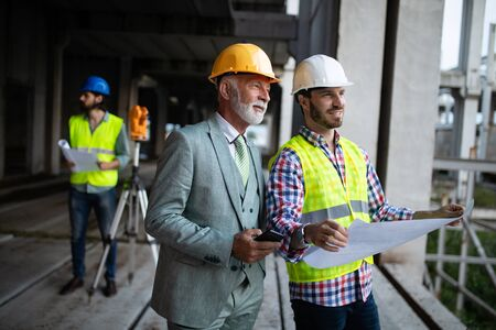 Confident team of architects and engineers working together on construction site Banco de Imagens