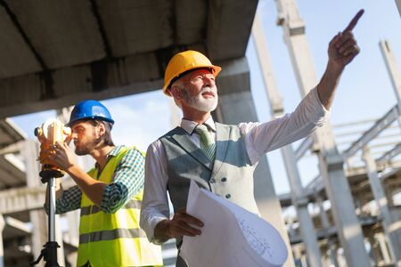 Engineer and construction site manager dealing with blueprints and plans