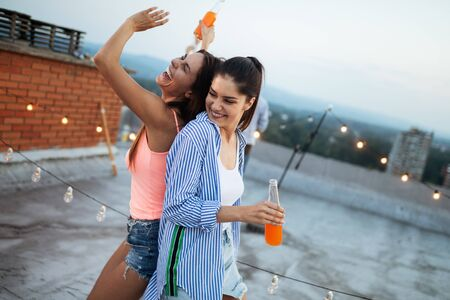 Beautiful women friends on the balcony having fun at party. Stock Photo